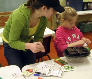 Whitney Schreder of Mount Vernon watches her daughter, Kaylie, 6, plant herb seeds Saturday, March 2, 2013, during the Mount Vernon Gardening and Local Foods Education Day. (photo/Cindy Hadish)
