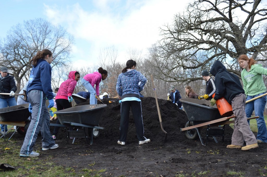 """Students and other volunteers load compost to use in the Harrison Elementary School garden on Saturday, April 13, 2013. The garden is part of the """"Kids On Course"""" program, started by golfer and Cedar Rapids native, Zach Johnson. (photo/Cindy Hadish)"""