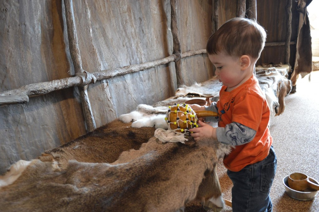 Ian Nelson, 1, of Marion, plays inside the longhouse display during the grand opening of the Wickiup Hill Learning Center's expansion on Saturday, April 13, 2013, near Toddville. (photo/Cindy Hadish)