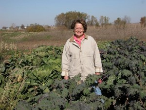 Laura Krouse stands in her kale field at her farm near Mount Vernon. Abbe Hills Farm has one of a growing number of CSA programs in Iowa. (photo courtesy of Laura Krouse)