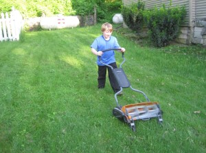 Calvin DeWitte, the author's 11-year-old son, has begun volunteering for lawn mowing duty since the lightweight reel lawn mower arrived. It's a struggle to get through tall grass, but fun on shorter turf. (photo by Dave DeWitte)