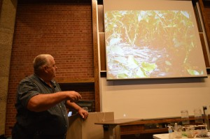Ohio farmer Dave Brandt points to a slide showing plants growing through his cover crops during the soil seminar at Coe College, sponsored by the NRCS. (photo/Cindy Hadish)