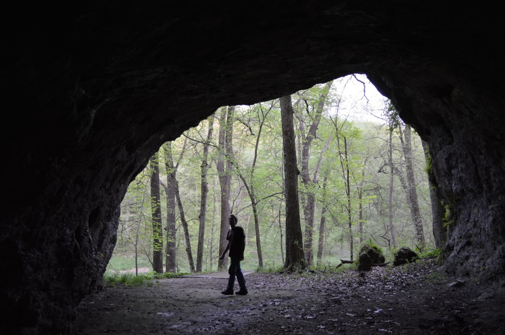 A visitor walks near the entrance of Horse Thief Cave at Wapsipinicon State Park near Anamosa. The cave is one of the notable natural features in the nearly 400-acre park. (photo/Cindy Hadish)