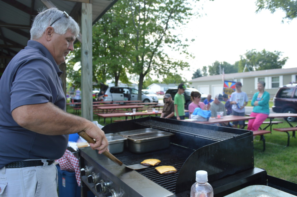 Rapid Creek Ranch owner Doug Darrow works the grill during the Oxford Farmers Market. A variety of businesses and organizations take turns cooking during the markets. (photo/Cindy Hadish)