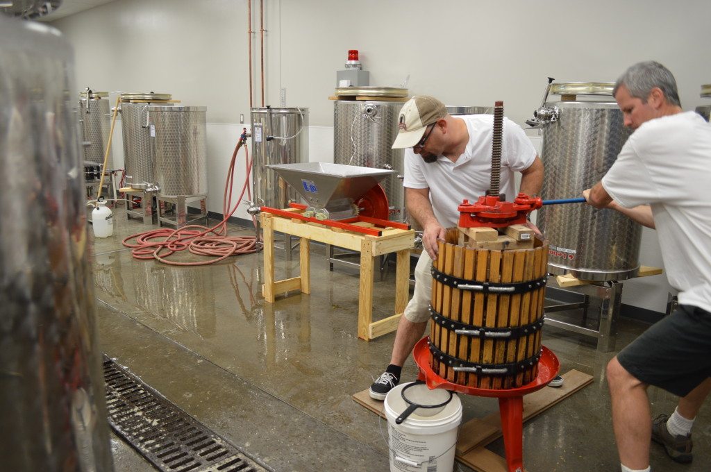 Classmates work the grape press at Kirkwood Community College to make Frontenac Blanc wine. (photo/Cindy Hadish)