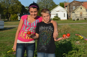 Cousins Kyra, 13, and Jordan, 11, show off some of their harvest at the Czech heritage garden in the New Bohemia district in Cedar Rapids. (photo/Cindy Hadish)
