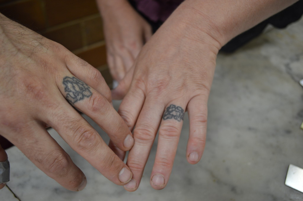 Andy and Lalanya Bodenbender, owners of Henry's Village Market, show their tattooed wedding bands. (photo/Cindy Hadish)