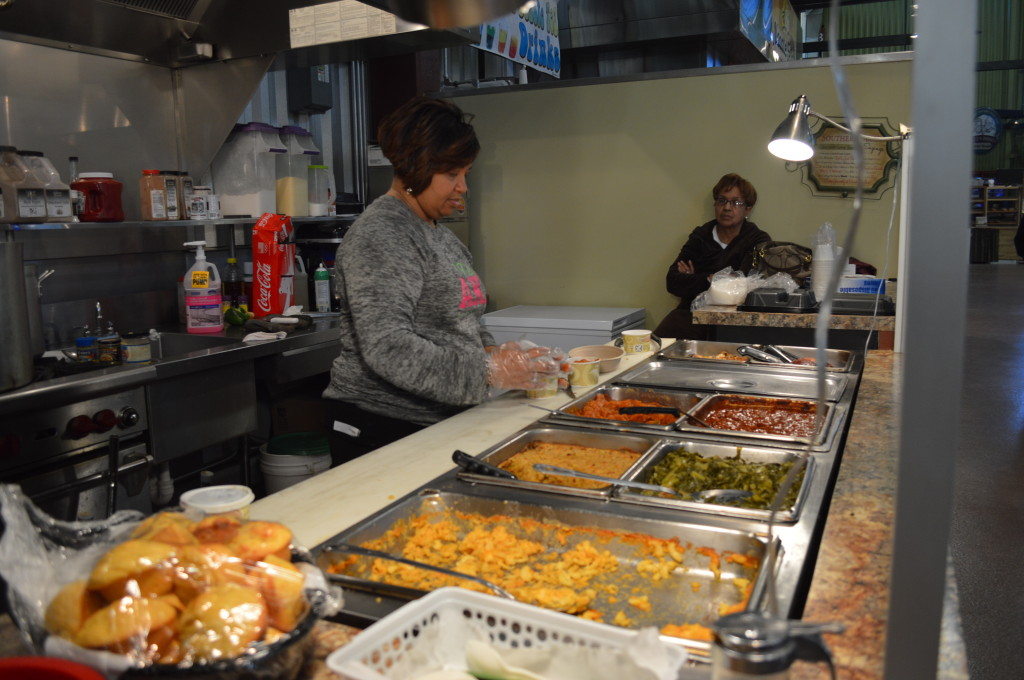 Co-owner Carol Simmons dishes up a meal on Feb. 22, 2014, at Iowa Soul Food Company at the NewBo City Market in Cedar Rapids. (photo/Cindy Hadish)