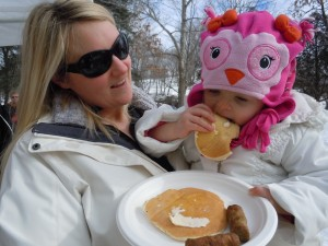 A young visitor takes a bit of a pancake at the 2013 Maple Syrup Festival at the Indian Creek Nature Center in Cedar Rapids, Iowa. This year's festival will be March 1 and 2. (photo/Cindy Hadish)