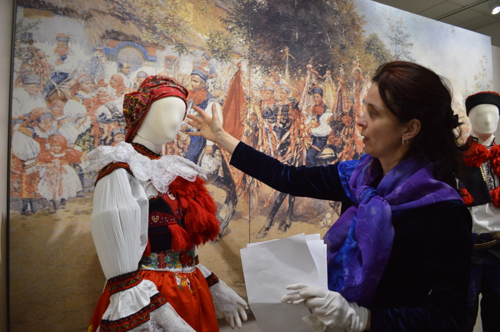 """Petra Červinková, who manages the ethnographic department at the National Museum in Prague, shows how traditional scarves are used by women in the Moravian region of the Czech Republic. Červinková traveled from Prague to Cedar Rapids to help set up the """"Celebrations!"""" exhibit, now open at the National Czech & Slovak Museum & Library. (photo/Cindy Hadish)"""