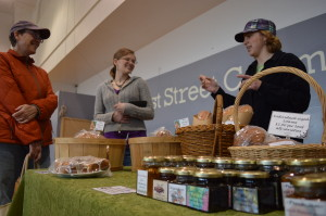Laura Strabala (right) and Danielle Martin (center) chat with a customer during the indoor Mount Vernon Farmers Market this spring. The two sisters are retiring from selling at farmers markets, but will continue as the market's managers. (photo/Cindy Hadish)