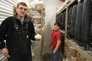 Todd Mills holds a lion's mane mushroom as his son Ethan looks on in the growing room of their mushroom operation in Columbus Junction. (photo/Cindy Hadish)