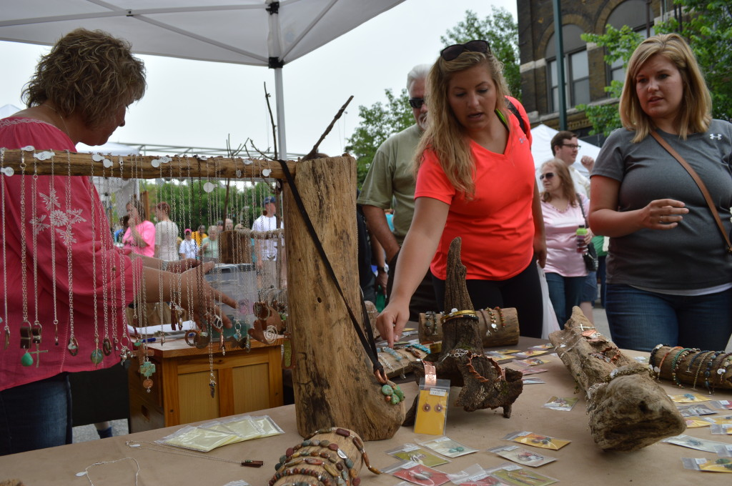 Customers look at necklaces and other items sold by Weeping Water Jewelry during the first Downtown Farmers Market of the season on Saturday, June 7, 2014. (photo/Cindy Hadish)