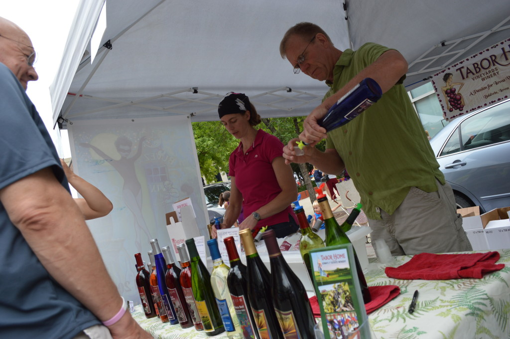 Paul Tabor, of Tabor Home Vineyards and Winery, pours samples for customers during the Downtown Farmers Market in Cedar Rapids, Iowa. (photo/Cindy Hadish)
