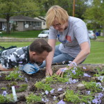 Friends of Noelridge volunteer Cindy Garlock, right, shows Goodwill Dayhab volunteer Ron Hunt how to  plant flowers at the Butterfly Garden at Noelridge Park in Cedar Rapids. (photo/Cindy Hadish)