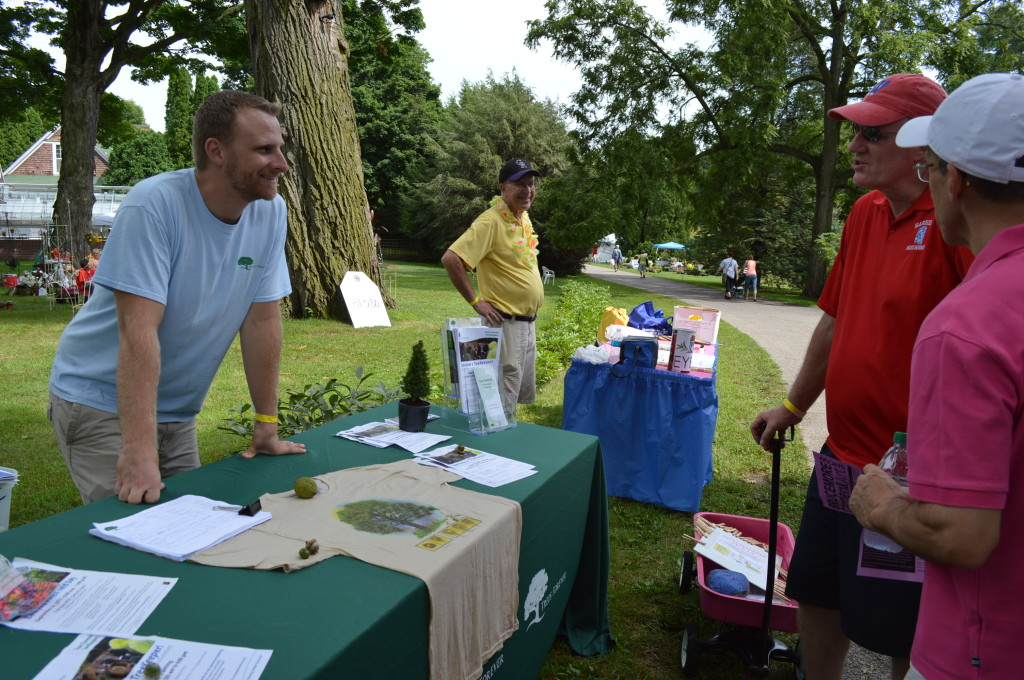 Dustin Hinrichs, left, of Trees Forever, and Dale Kueter, of Eye 380, talk to passers-by at their booths on Saturday, Aug. 23, at the Brucemore Garden & Art Show. (photo/Cindy Hadish)