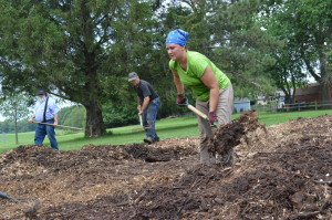 Mulch is raked into place during a Backyard Abundance mulching party in July 2014 at Wetherby Park in Iowa City. (photo/Cindy Hadish)