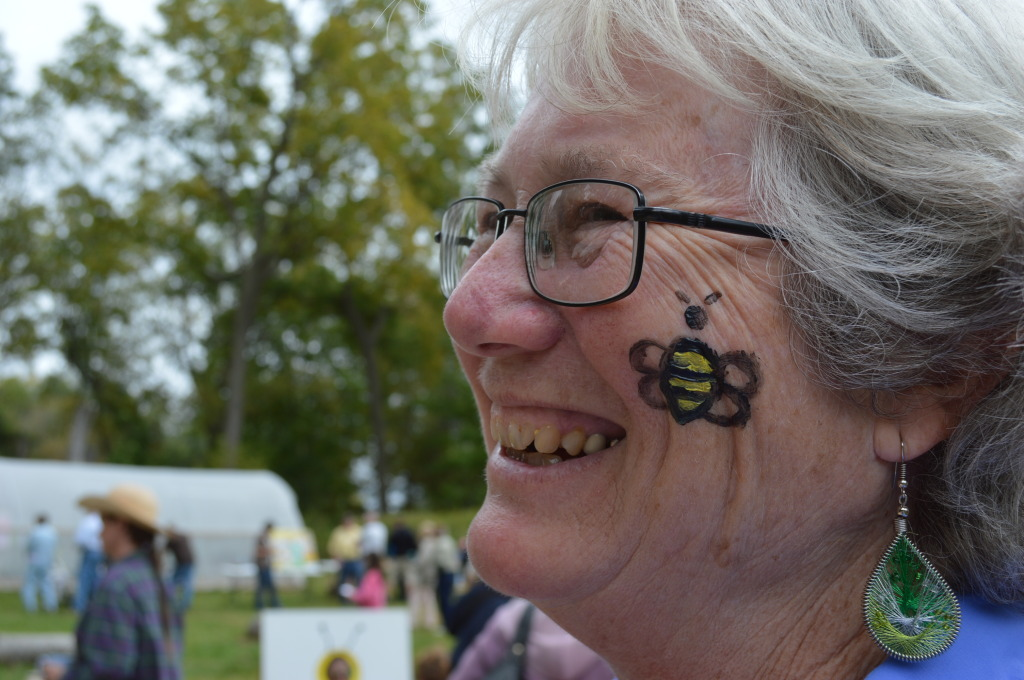 Jan Aiels, Education Director at the Indian Creek Nature Center, gets in the spirit of Honey Fest with a bee-utiful face-painting. (photo/Cindy Hadish)