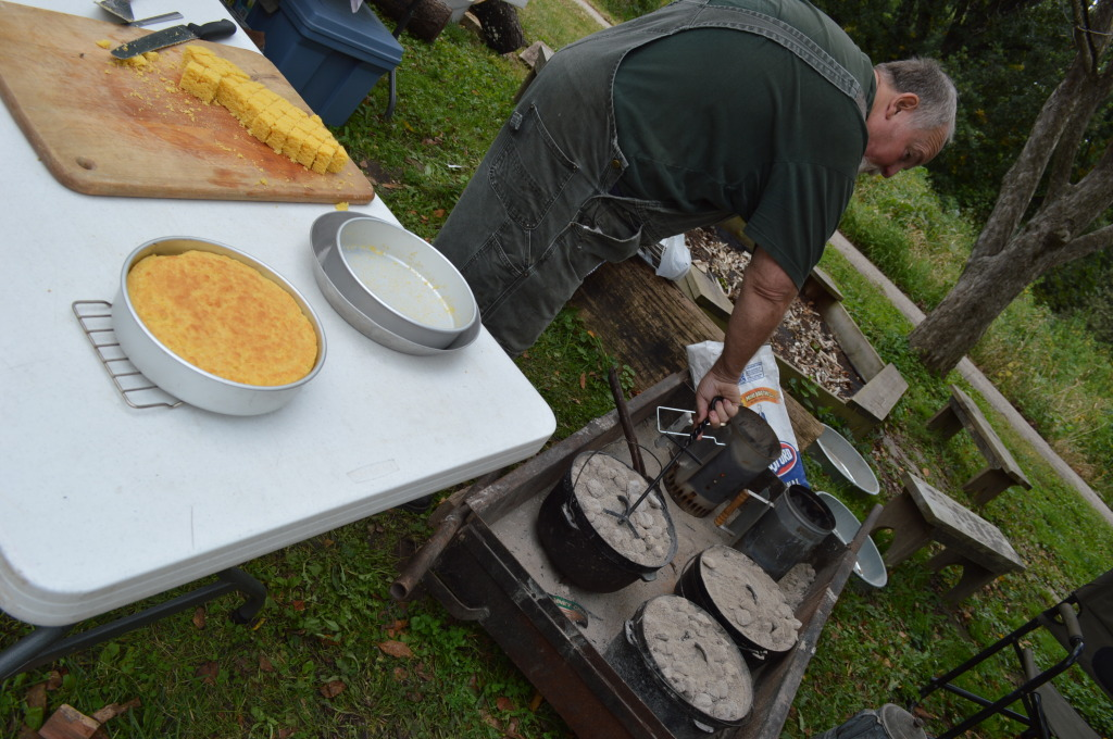 Volunteer Mike Duss bakes cornbread in Dutch ovens during Honey Fest on Sept. 21, 2014. (photo/Cindy Hadish)