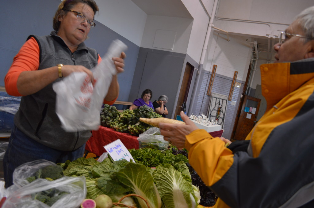 Laura Krouse, left, talks to a customer during the indoor Mount Vernon Farmers Market, where Krouse can often be found on Saturday mornings. (photo/Cindy Hadish)