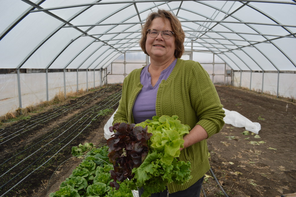 Laura Krouse is shown with some of the produce grown in her hoophouse in rural Mount Vernon, Iowa. (photo/Cindy Hadish)
