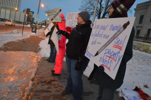 Opponents of the Keystone XL and Bakken pipelines hold signs Tuesday, Jan. 13, 2015, on the Third Avenue Bridge in downtown Cedar Rapids. (photo/Cindy Hadish)