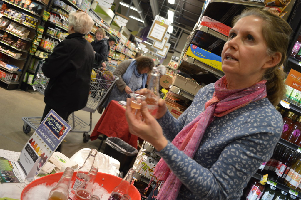 Samples of Shaktea Kombucha are poured for customers during the grand opening of New Pioneer Food Co-op's new store in Cedar Rapids. (photo/Cindy Hadish)