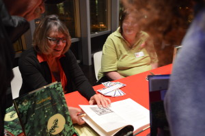 "Diane Ott Whealy signs copies of her book, ""Gathering: Memoir of a Seed Saver"" on Thursday, March 26, at the Cedar Rapids Public Library. (photo/Cindy Hadish)"
