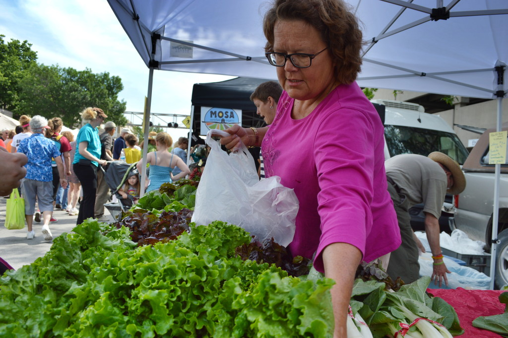 Laura Krouse of Abbe Hills Farm in rural Mount Vernon bags lettuce for a customer at the Downtown Farmers Market. (photo/Cindy Hadish)