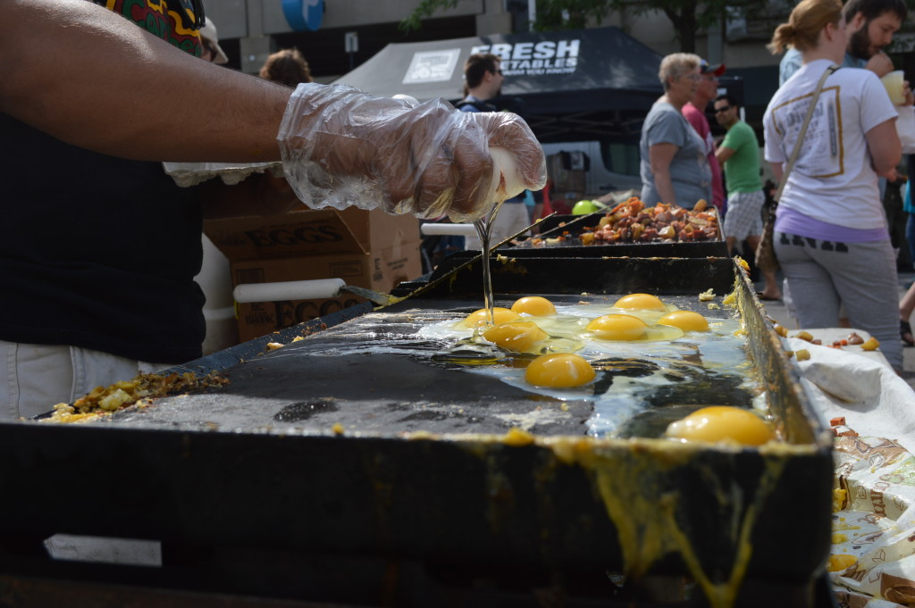Food is prepared by the Caribbean Kitchen during the Downtown Farmers Market on June 6, 2015. (photo/Cindy Hadish)