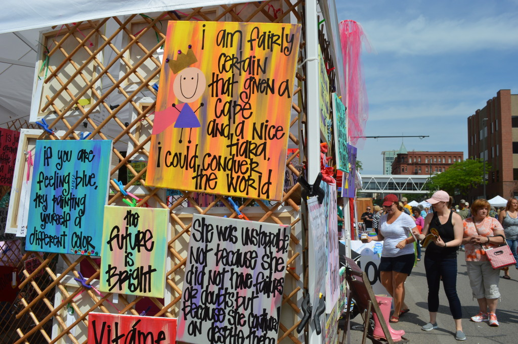Signs are sold by Girl in the Pink Rainboots during the Downtown Farmers Market in Cedar Rapids. (photo/Cindy Hadish)