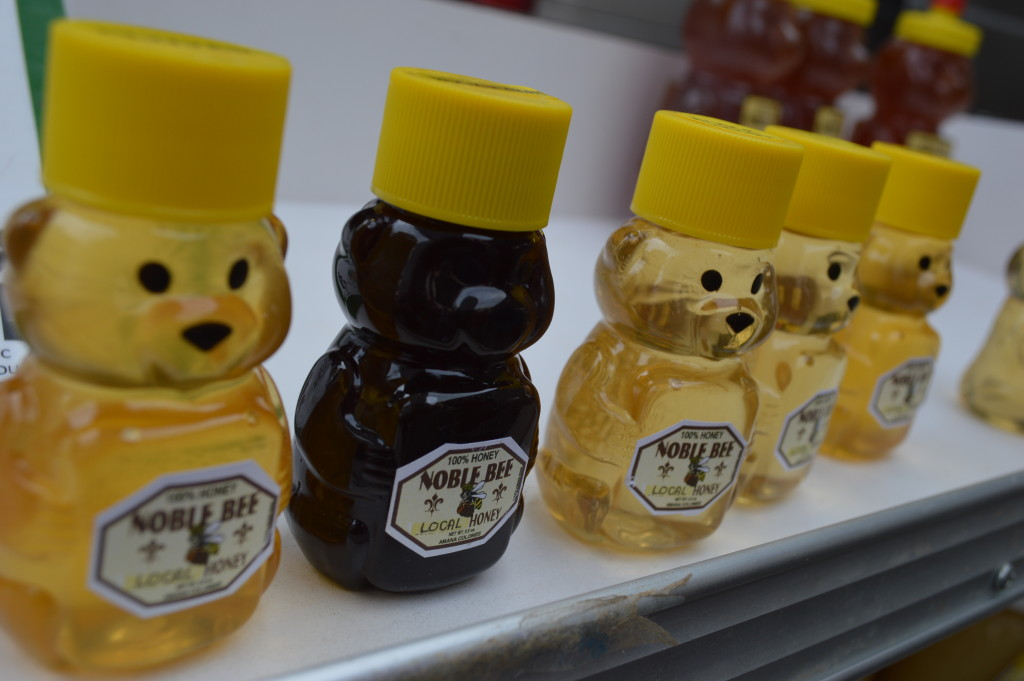 Miniature bottles of honey line one of the shelves of the Noble Bee booth at the Downtown Farmers Market on Saturday, June 6, 2015. (photo/Cindy Hadish)