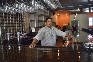 Co-owner Lenny Sims stands behind the bar of Sauce Bar & Bistro, on Tuesday, June 23, 2015, in Czech Village. (photo/Cindy Hadish)