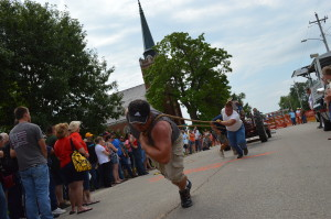 """Spectators watch the """"human tractor pull"""" in Chelsea, Iowa, during the town's sesquicentennial celebration in 2014. Chelsea is among the communities participating in a """"Tama Town Mystery"""" this summer. (photo/Cindy Hadish)"""