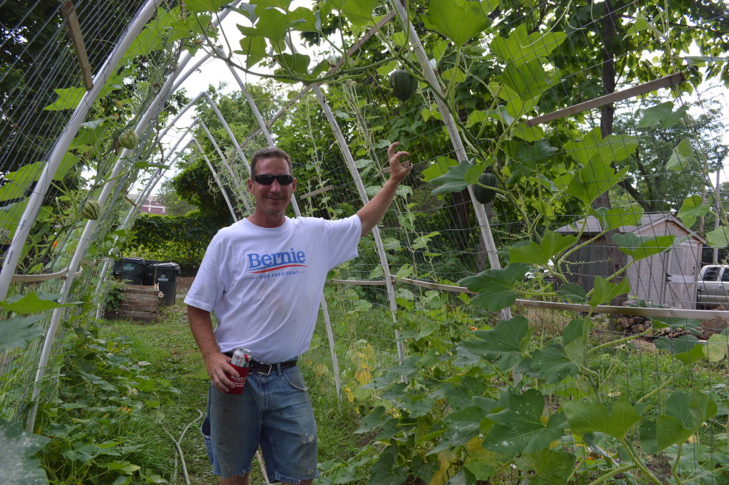Ed Thornton stands under one of the trellises he constructed during a garden party Saturday, Aug. 8, 2015, at his new garden site in southeast Cedar Rapids. (photo/Cindy Hadish)