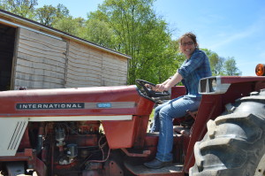 An International tractor that her grandfather owned continues the family farming legacy for Kate Edwards of Wild Woods Farm near Solon, Iowa. (photo/Cindy Hadish)