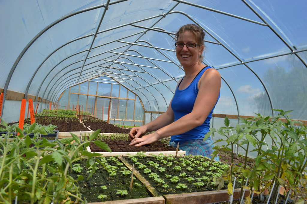 Kate Edwards takes a break from planting inside her high tunnel at Wild Woods Farm near Solon. (photo/Cindy Hadish)