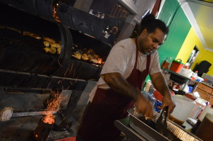 Patrick Rashed of Caribbean Kitchen checks the chicken off the grill at Market After Dark. Rashed said business was excellent at the first nighttime market in Cedar Rapids. (photo/Cindy Hadish)