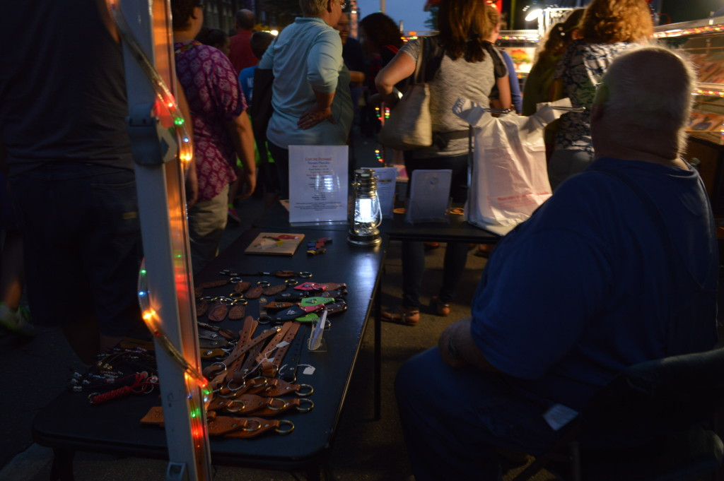 Festival lighting shines on Larry and Helen Kubalek's Wood Visions stand at Market After Dark. (photo/Cindy Hadish)