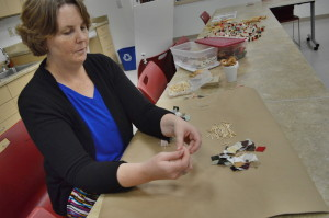 Jan Stoffer demonstrates how to make a handmade fabric Christmas tree garland at the museum. (photo/Cindy Hadish)