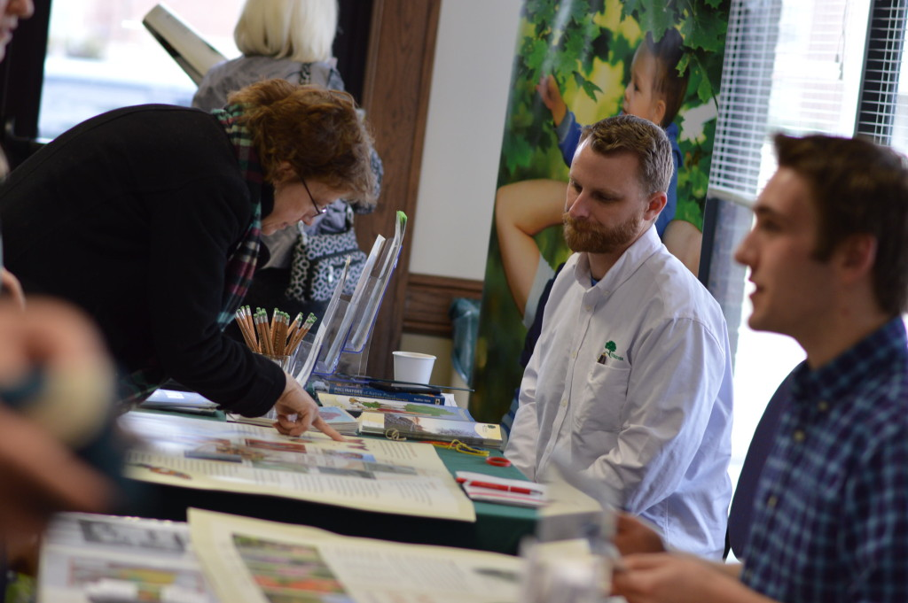 Dustin Hinrichs, (center) of Trees Forever, talks to visitors at the vendor booths during the Winter Gardening Fair in Cedar Rapids. (photo/Cindy Hadish)