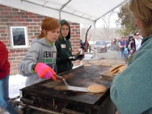 Volunteers flip pancakes during a previous Maple Syrup Festival at the Indian Creek Nature Center in Cedar Rapids, Iowa. The event will be held in the Nature Center's barn for the last time in 2016. (photo/Cindy Hadish)