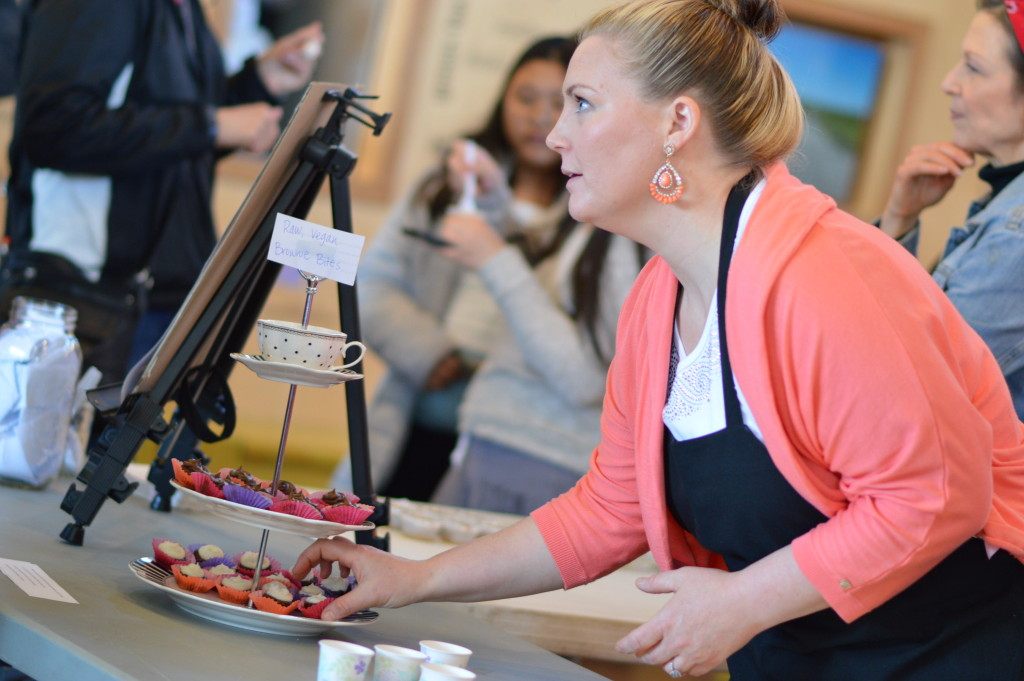 Jessica LaFayette adds brownie bites to a tray while talking to customers at the Rawlicious preview tasting at the NewBo City Market in Cedar Rapids, Iowa. (photo/Cindy Hadish)
