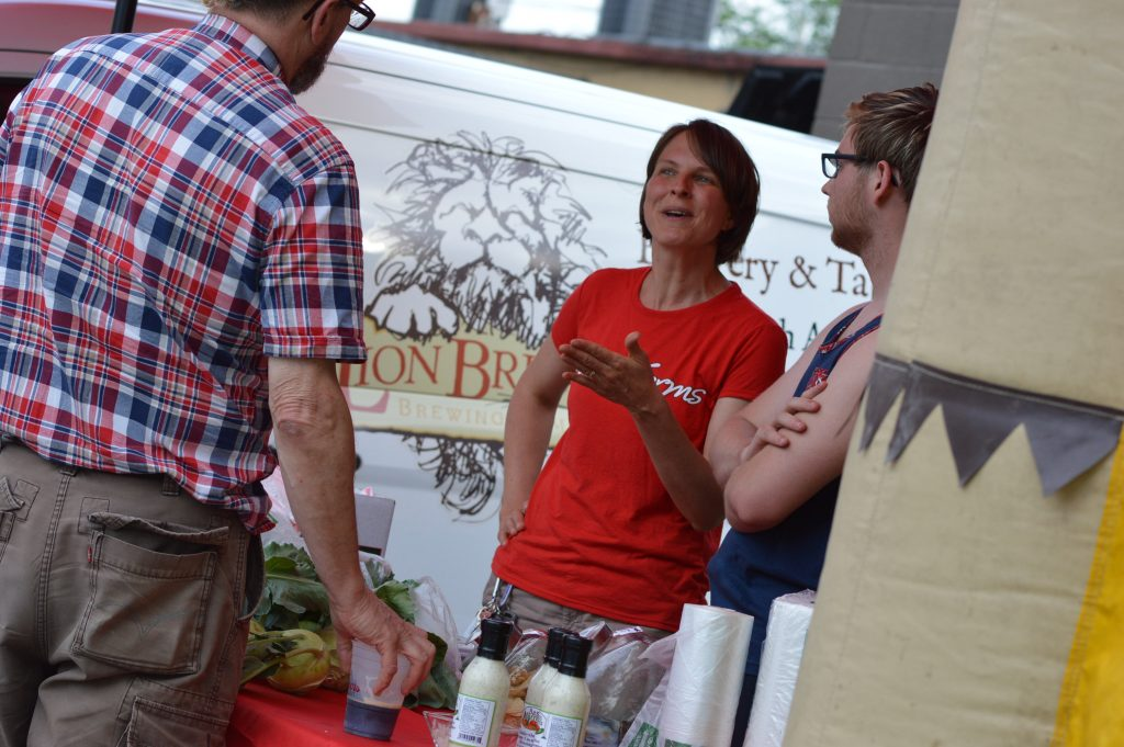 Laurie Carrick, produce specialist for Bass Farms of Mount Vernon, Iowa, talks to a customer at the Lion Bridge Farmers Market in Czech Village. (photo/Cindy Hadish)