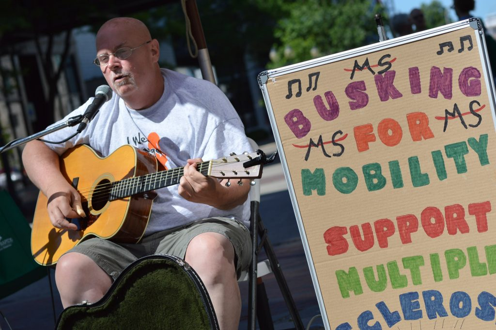 Singer Mark Brown performs during the Downtown Farmers Market as Busking for Mobility to raise money to support the Multiple Sclerosis Society. (photo/Cindy Hadish)