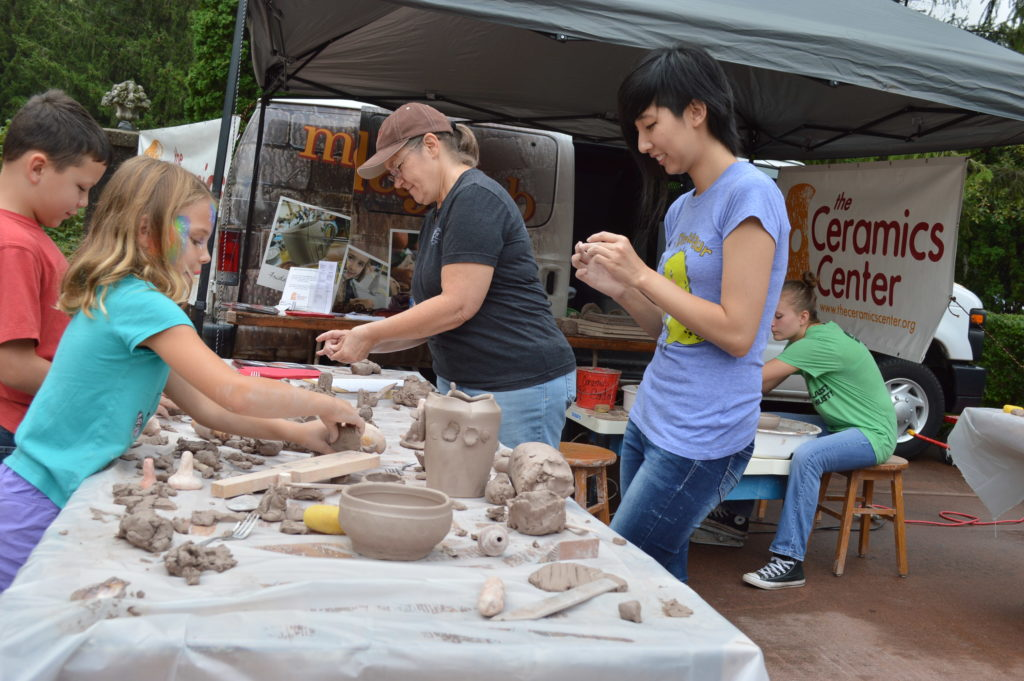Children make their own creations at the Ceramics Studio booth during the Brucemore Garden & Art Show. (photo/Cindy Hadish)