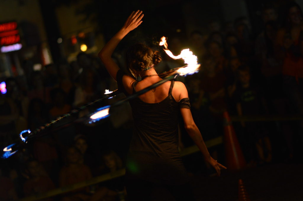 A performer spins a hula hoop lit by fire during Market After Dark in downtown Cedar Rapids. (photo/Cindy Hadish)