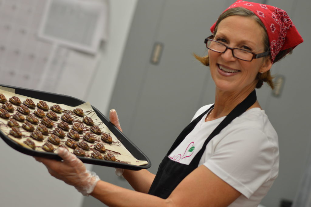 Laurie Moritz, owner of Sweet Raw Joy, is shown with a tray of Baby Sea Turtles in the kitchen of New Pioneer Food Co-op in Cedar Rapids, Iowa. (photo/Cindy Hadish)