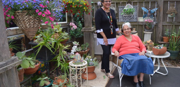 Monica Morley and her mother, Elena Murillo, seated, are shown in the courtyard area of their garden earlier this spring. The succulent plants, to the left, are all wintered over in the basement of their Cedar Rapids home and brought back outdoors for the season. Flowers in the hanging baskets include million bells (Calibrachoa,) lobelia and lantana. (photo/Cindy Hadish)
