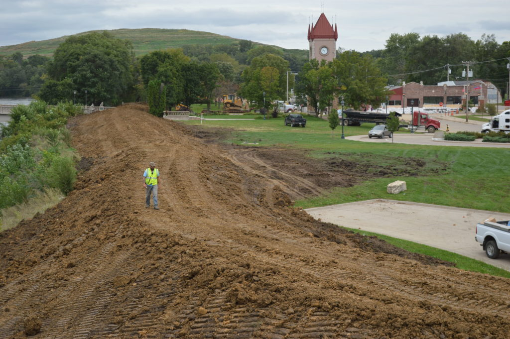 A worker crosses an earthen berm being constructed at the edge of Czech Village in Cedar Rapids on Sept. 25, 2016. (photo/Cindy Hadish)
